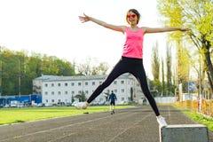 A menina adolescente bonita salta no estádio fotos de stock royalty free