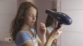 A menina adolescente bonita seca o cabelo um hairdryer no vídeo da metragem do estoque do movimento lento do banheiro vídeos de arquivo