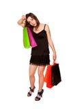 Menina adolescente cansado com os sacos de compras que saem da loja. imagem de stock royalty free