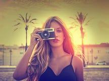 Menina adolescente com a câmera retro da foto no por do sol foto de stock