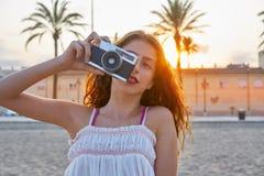 Menina adolescente com a câmera retro da foto no por do sol imagens de stock royalty free