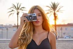 Menina adolescente com a câmera retro da foto no por do sol imagem de stock
