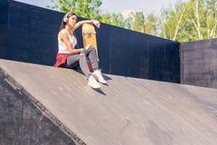 Menina adolescente com m?sica de escuta do skate Fora, estilo de vida urbano imagem de stock royalty free