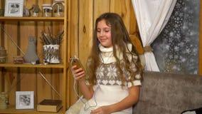 Menina adolescente com música de escuta dos fones de ouvido de um smartphone em casa filme