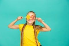 A menina adolescente com pirulito colorido em um fundo azul Fotografia de Stock Royalty Free