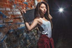 Menina adolescente com placa do patim, estilo de vida urbano Fotografia de Stock Royalty Free