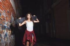 Menina adolescente com placa do patim, estilo de vida urbano Imagens de Stock Royalty Free