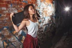 Menina adolescente com placa do patim, estilo de vida urbano Imagens de Stock