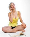 Menina adolescente com telefone móvel e livro Fotos de Stock Royalty Free