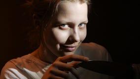 Menina adolescente com uma faca grande e um sorriso demoníaco, cena escura do filme de terror, 4K UHD filme
