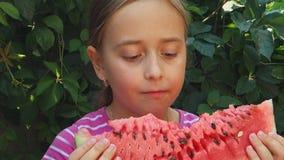 A menina adolescente come uma melancia doce, suculenta no fundo das hortaliças A criança aprecia uma fatia grande de melancia filme
