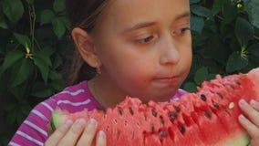 A menina adolescente come uma melancia doce, suculenta no fundo das hortaliças A criança aprecia uma fatia grande de melancia vídeos de arquivo