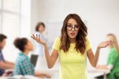 Menina adolescente confusa do estudante nos vidros na escola foto de stock