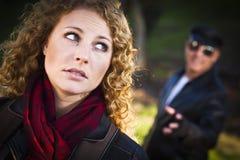 Menina adolescente consideravelmente nova com o homem que espreita atrás dela fotos de stock