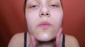 Menina adolescente da beleza que aplica o creme em sua cara, 4K filme