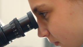 Menina adolescente da escola no laboratório que estuda a biologia, olhando através do microscópio Close-up video estoque