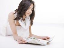 Menina adolescente de Oung na leitura branca do vestido no assoalho Imagens de Stock Royalty Free