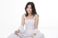Menina adolescente de Oung na leitura branca do vestido no assoalho Imagens de Stock