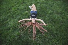 Menina adolescente de sorriso com as tranças da cor por todo o lado na grama Fotografia de Stock Royalty Free