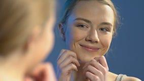 Menina adolescente de sorriso com a composi??o que olha no espelho, apreciando a beleza, cosm?ticos video estoque