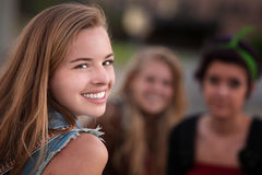 Menina adolescente de sorriso com dois amigos Fotografia de Stock