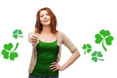 Menina adolescente de sorriso com o trevo que mostra os polegares acima Fotografia de Stock