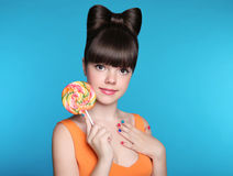 Menina adolescente de sorriso da beleza que come o pirulito colorido H atrativo Fotografia de Stock
