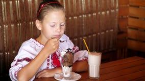 A menina adolescente de sorriso feliz, criança come o gelado em um café é vestida na roupa nacional ucraniana, bordado video estoque