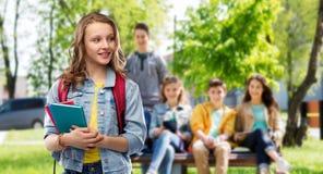 Menina adolescente de sorriso feliz do estudante com saco de escola fotos de stock royalty free