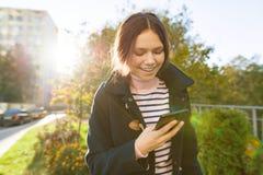 Menina adolescente de sorriso nova com telefone celular, dia ensolarado do outono, menina no revestimento, hora dourada fotografia de stock royalty free