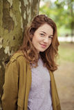 Menina adolescente de sorriso que inclina-se contra o tronco de árvore Foto de Stock Royalty Free