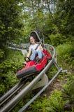 Menina adolescente de sorriso que monta para baixo em uma montanha russa exterior em um dia de verão morno fotografia de stock royalty free