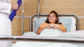 Menina adolescente de sorriso que senta-se na cama de hospital