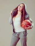 Menina adolescente desportiva na capa que guarda o basquetebol Foto de Stock Royalty Free