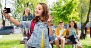Menina adolescente do estudante que toma o selfie pelo smartphone imagens de stock royalty free