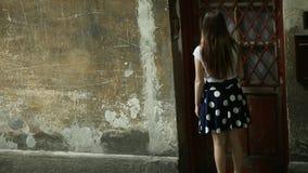 A menina adolescente do gute anda acima à casa, soa a porta e as folhas filme