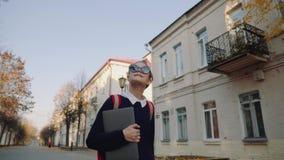 Menina adolescente do moderno bonito que anda abaixo da rua velha e do sorriso da cidade Estudante com o portátil vermelho da ter video estoque