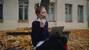 Menina adolescente do moderno bonito que senta-se em um passeio na rua da cidade do outono e no laptop de trabalho Utilização da  video estoque