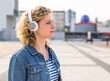 Menina adolescente do moderno que sorri e que escuta a música na cidade Fotos de Stock Royalty Free