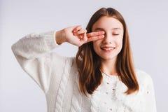 Menina adolescente emocional em uma camiseta feita malha branca em um claro - fundo cinzento Espa?o para o texto imagens de stock royalty free