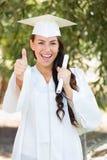 Menina adolescente entusiasmado da raça misturada na graduação que guarda o diploma imagens de stock