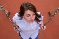 Menina adolescente entusiasmado feliz em um balanço chain, parque do verão exterior Imagem de Stock