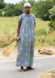 A menina adolescente-envelhecida jovens no vestido tradicional ajuda com harv do painço Imagem de Stock Royalty Free
