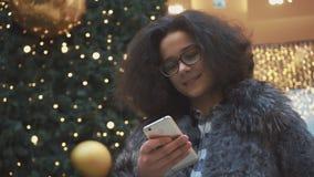 A menina adolescente escreve uma mensagem no telefone closeup video estoque