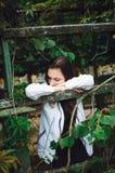A menina adolescente está na rua na perspectiva das folhas verdes imagens de stock