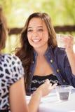 Menina adolescente expressivo que tem bebidas e que fala com amigo fotografia de stock
