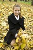 A menina adolescente feliz agarra um grupo das folhas amarelas Fotos de Stock