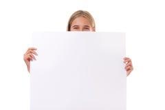 Menina adolescente feliz atrás da placa vazia, isolada Fotografia de Stock Royalty Free