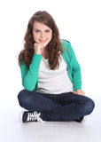Menina adolescente feliz do estudante que senta equipado com pernas transversal Imagens de Stock