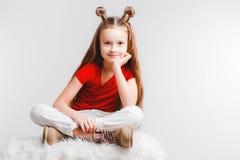 A menina adolescente feliz emocional que veste um t-shirt vermelho e chifres deu forma ao cabelo imagens de stock